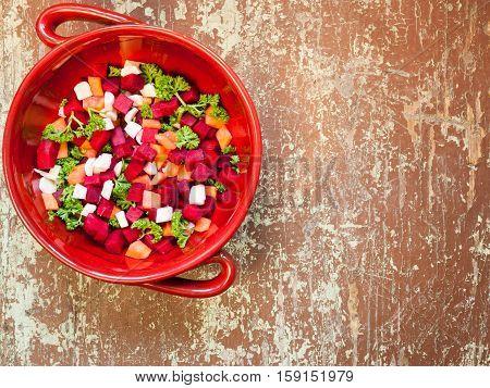 Clay bowl full of fresh vegetable salad