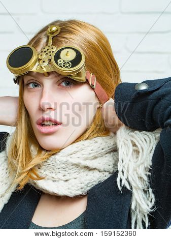 Pretty girl young cute beautiful woman or watchmaker with watch mechanical metallic gears and cogwheels on red hair on white brick wall
