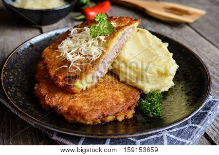 Pork Cutlets Coated In Potato Batter, Studded With Cheese And Served With Mashed Potato