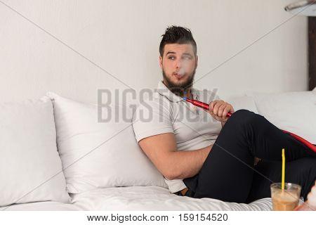 Young Man Smoking Shisha At Arabic Restaurant
