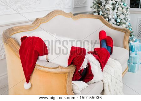 Santa Claus resting on a sofa at home. Funny Santa lying, christmas pause