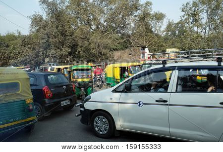 DELHI, INDIA - FEBRUARY 13 : Traffic jam with rickshaws, motorbikes, cars and pedestrians on local city street in Delhi, India on February 13, 2016. Traffic jam is the main problem of transportation