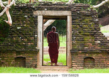 ANRUADAPURA - NOVEMBER 18 : BUDDHIST STANDING AT THE DOORSTEPS IN ANCIENT MONASTERY IN JUNGLE ON NOVEMBER 18 2015 IN ANRUADAPURA SRI LANKA