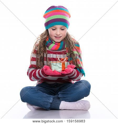 Smiling Pretty Little Girl Wearing Coloful Knitted Scarf, Hat And Gloves, Holding Christmas Gift Iso