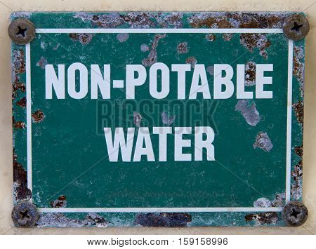 An old green and white non potable water sign.