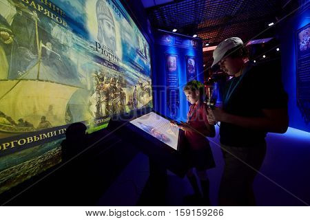 MOSCOW, RUSSIA - AUG 30, 2016: Girl and boy (with model releases) stand near screen in history park Russia - My History at VDNKh. Museum is designed for simultaneous presence up to 5 thousand people.