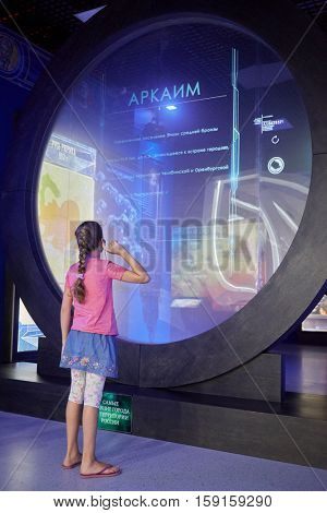 MOSCOW, RUSSIA - AUG 30, 2016: Girl (with model release) at multimedia screen in history park Russia - My History in VDNKh. Most ancient cities on Russia territory inscription at bottom.