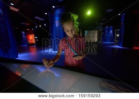 MOSCOW, RUSSIA - AUG 30, 2016: Girl (with model release) scroll text on interactive screen in history park Russia - My History in VDNKh. Museum presents key points of development of Russian state.