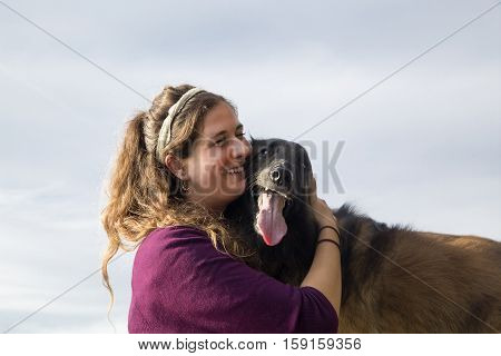 Twenty-year-old female smiling and hugging her dog to her face