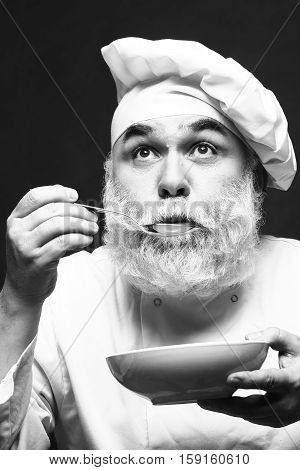 Bearded man cook in hat tasting food with spoon in studio black and white
