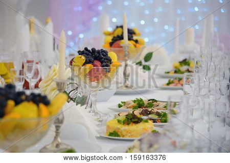 Table served dishes and candles. A festive reception at the table with food. Luxury table for a holiday celebration. Snacks and fruits on the occasion.