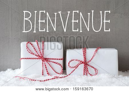 French Text Bienvenue Means Welcome. Two White Christmas Gifts Or Presents On Snow. Cement Wall As Background. Modern And Urban Style.