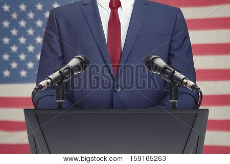 Businessman Or Politician Making Speech Behind The Pulpit With Usa Flag On Background