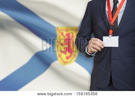 Businessman Holding Badge On A Lanyard With Canadian Province Flag On Background - Nova Scotia