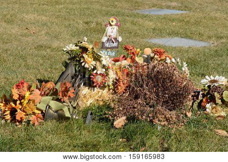Graveside decoration of artificial flowers, autumn scarecrow and sign