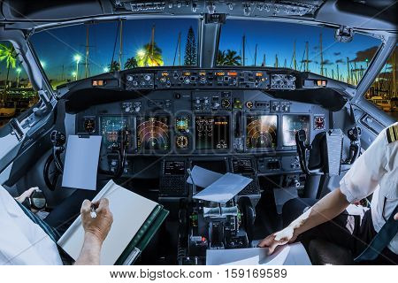 Airplane cockpit flying on Ala Wai Harbor, Honolulu by night, Oahu, Hawaii, with pilots arms and blank white papers for copy space.