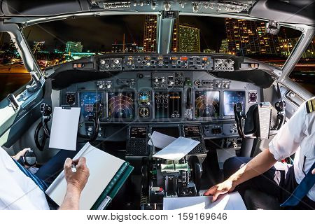 Airplane cockpit flying on Honolulu skyline by night, Oahu, Hawaii, with pilots arms and blank white papers for copy space.