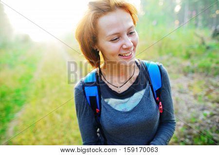 Young pretty red-haired girl in a sports Jersey with a backpack walking on a country road and laughing merrily on a Sunny summer day on blurred background close up.