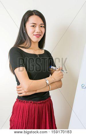 Beautiful Asian Woman Presenting On A Flipchart