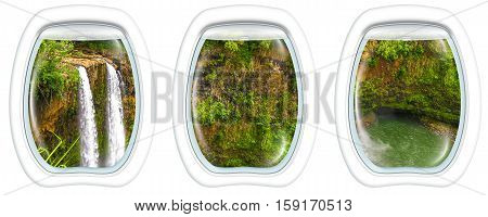 Three plane windows on ropical Manawaiopuna Falls also called Jurassic Park Falls, Kauai, Hawaii, United States, from a plane on the porthole windows. Copy space.
