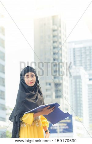 Young Asian Muslim Business Woman Smiling And Holding File Document And Standing At Capital City. Be