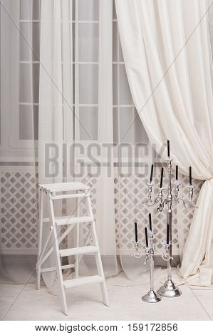 White Ladder Near Classic Silver Candle Holder In Living Room With Big Windows