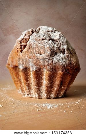 closeup of cupcake with powdered shugar with brown textured background