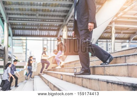 Businessman And Business Woman Up The Stairs In A Rush Hour To Work.