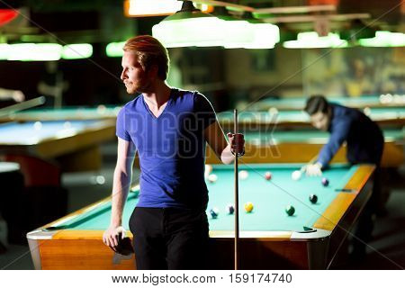 Portrait of a young man playing snooker