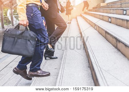 Couple Businessman And Business Woman Up The Stairs In A Rush Hour To Work.