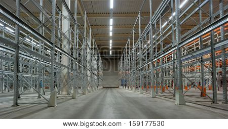 Interior of a warehouse with racks. Long rows of racks converge towards the center of the photo.