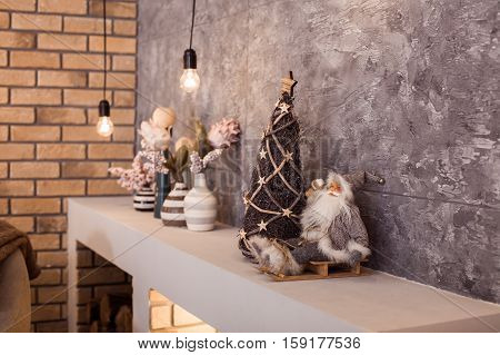 Small Santa Claus Sitting At The Upper Part Of Contemporary Fireplace.
