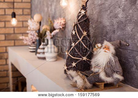 Small Santa Claus In Eyeglasses Sitting At The Sled