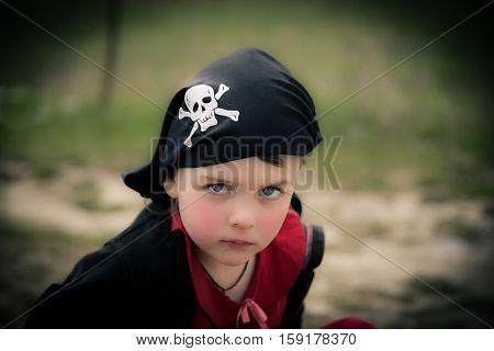 closeup view of amazing beautiful pirate little girl wearing black bandana with skull and bones