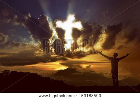 Silhouette of man praying to god with ray of light shaping cross on the sky