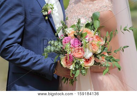Beautiful Bridal Bouquet In Hands Of The Bride. Wedding Bouquet Of Peach Roses By David Austin,  Sin