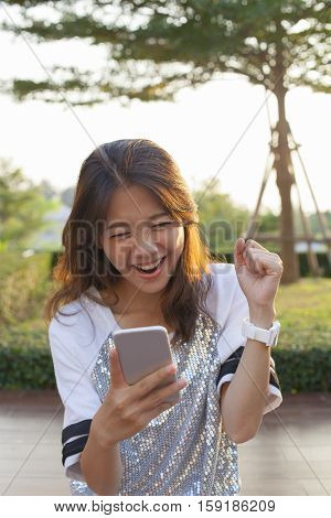 young asian woman watching to mobile phone screen with surprising and happiness face