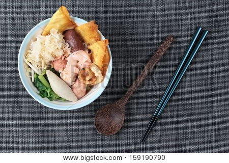 Thai noodle with pink tofu soup topped rugby fishball ,wonton ,porkball ,boiled porkblood ,pork rind ,coriander and white mushroom call Yen Ta Fo in Thai