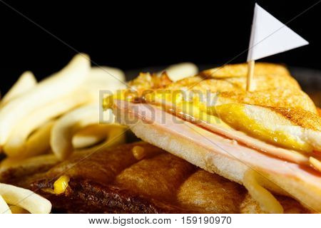 Sandwich ham cheese with frenchfries on wood plate and black background