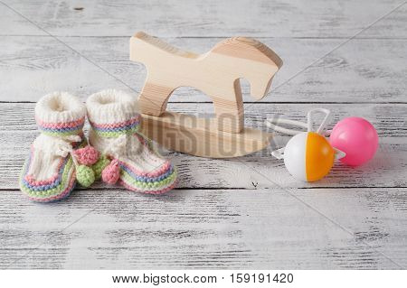 Birthday Invitation. Rattle, Wood Horse  And Knitted Booties For The Newborn