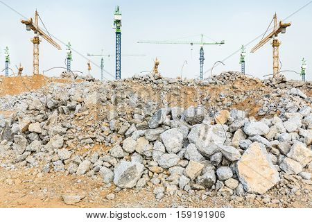pieces of concrete and brick rubble debris in front of giant cranes on construction site