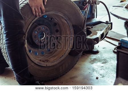 Mechanic Changing Tire With Bead Breaker Tool