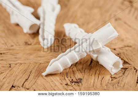 Closeup heap of plastic straddling dowel, industrial object
