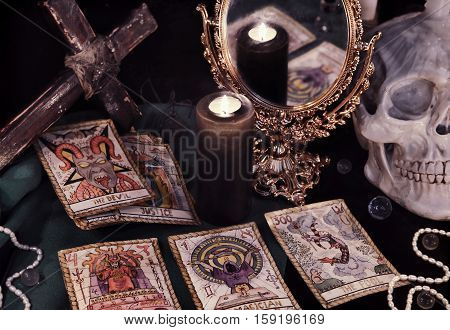 Esoteric still life with the Tarot cards, cross, mirror and skull in candle light. Halloween concept, fortune telling ritual with occult symbols, divination rite. Vintage objects on witch table