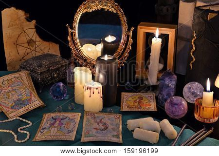 Divination rite with candles, the tarot cards, mirror and crystals. Halloween concept, black magic ritual or mystic spell with occult and esoteric symbols. Vintage objects on witch table