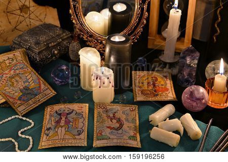 Magic still life with crystals, the Tarot cards and candles reflected in mirror. Halloween concept, mystic fortune telling ritual with occult symbols, divination rite. Vintage objects on witch table