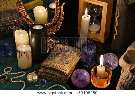 Mystic still life with the Tarot cards, mirror and burning candles.  Halloween concept, black magic ritual or spell with occult and esoteric symbols, divination rite. Vintage objects on witch table