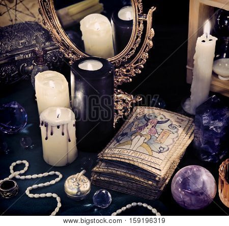 Black magic still life with the Tarot cards, mirror and crystal balls in candle light. Halloween concept, mystic fortune telling ritual, divination rite. Vintage objects on witch table