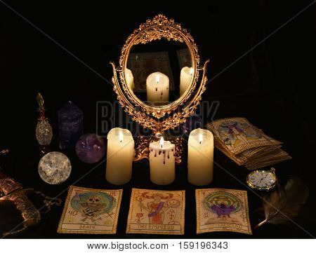 Fortune telling ritual with the Tarot cards, mirror, crystals and vintage objects. Halloween concept, black magic still life or witch spell with occult and esoteric symbols, divination rite