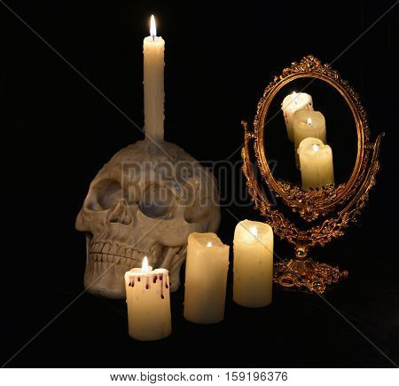 Mystic still life with skull, mirror and burning candles in the darkness. Halloween concept, black magic ritual or spell with occult and esoteric symbols, divination rite. Vintage objects on table